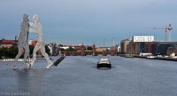 Ein Sechs-Wagen-Zug der U1 passiert auf der Oberbaumbrücke die Skulptur Molecule Man in der Spree.